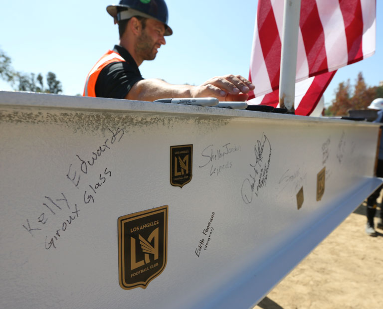 Members of the LAFC and Cal State LA sign the last pole at the construction site.