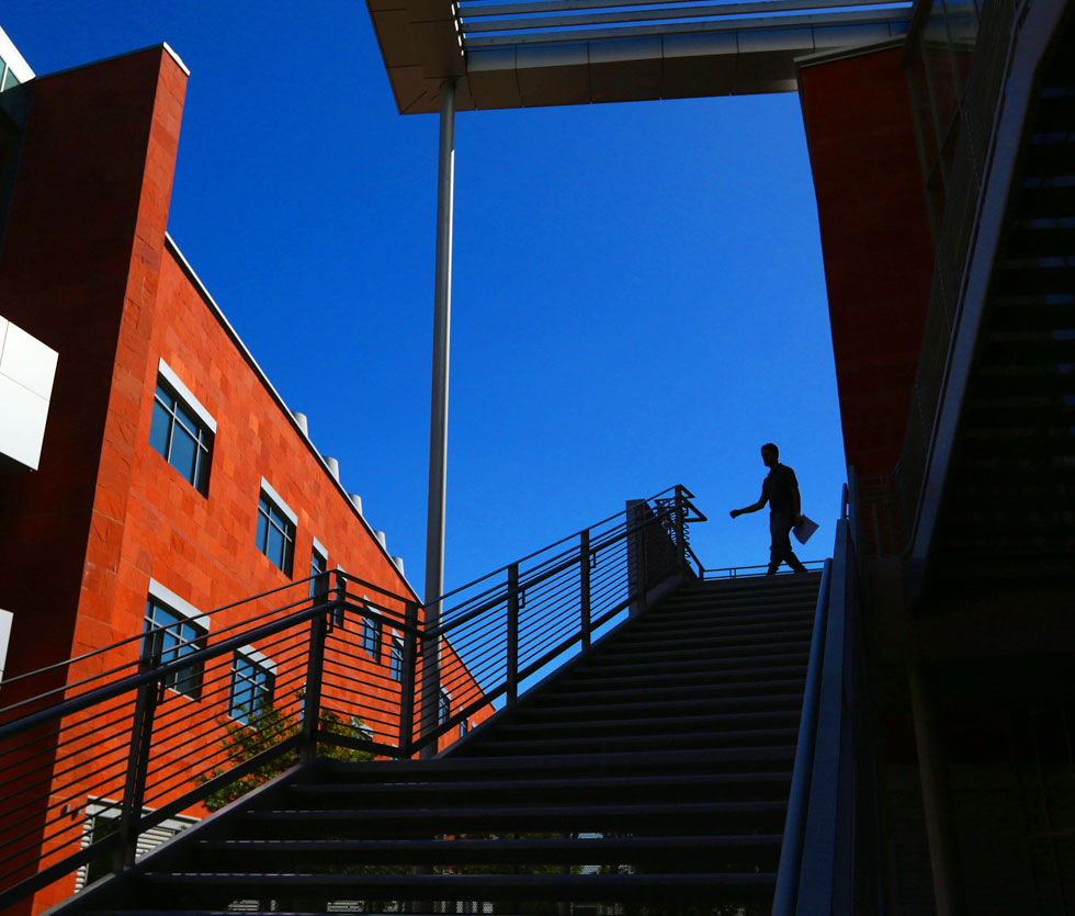 Person walking down staircase of La Kretz Hall with a vibrant blue sky behind them.