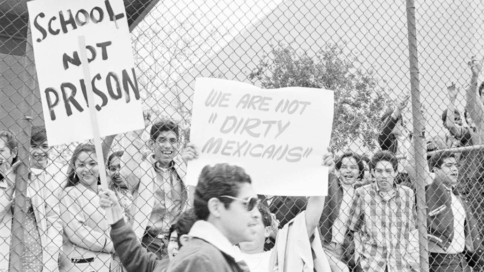 """Cal State LA students during the walkouts holding protest signs. One reading """"We are not 'Dirty Mexicans'"""" and the other reading """"School Not Prison""""."""