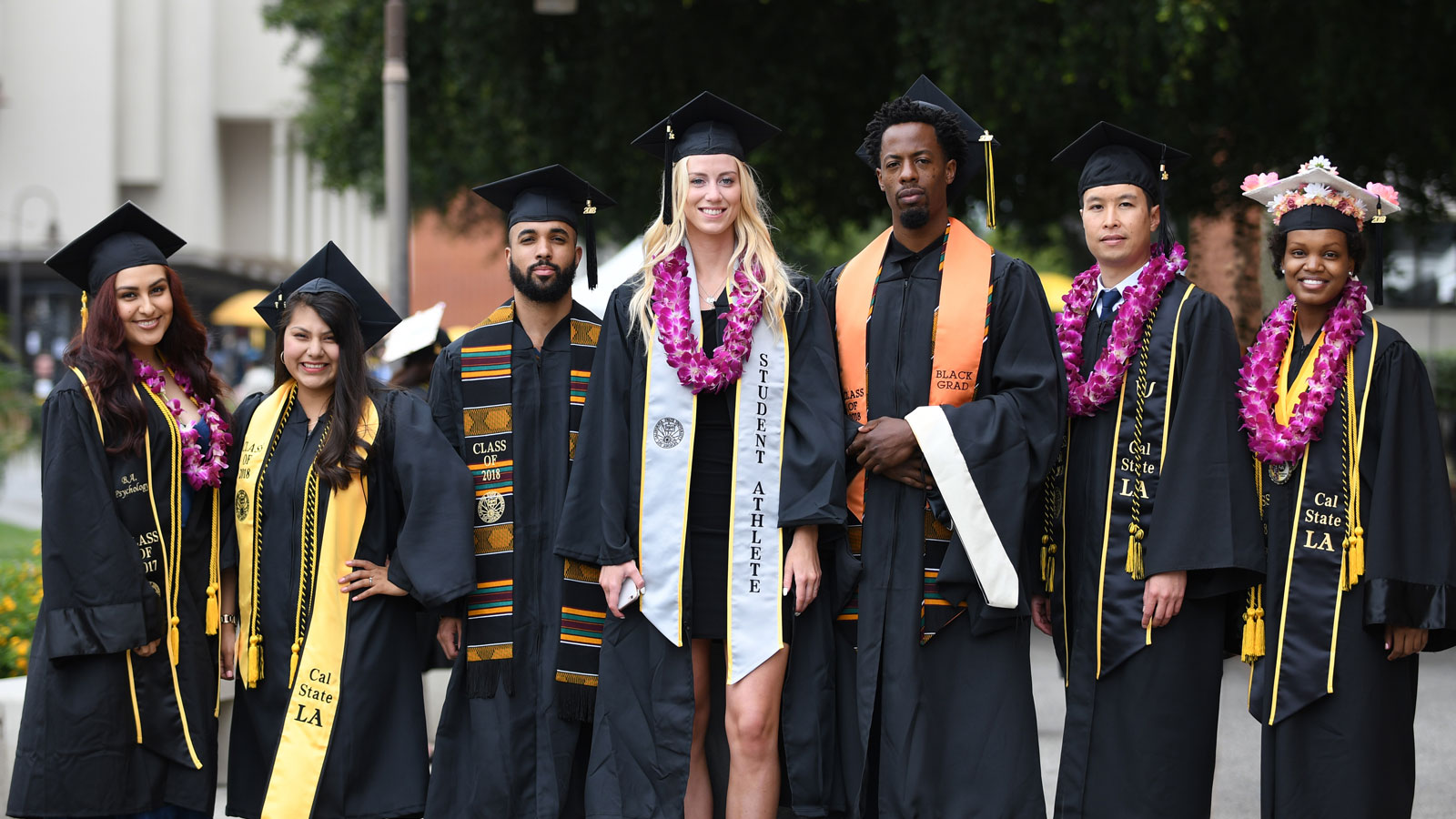 Cal State LA graduates posing with their caps and gowns